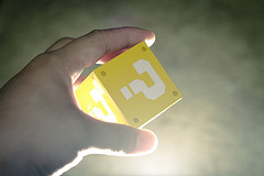 Mão segurando um cubo amarelo com ponto de interrogação.