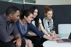 Grupo de jovens sentados em frente ao notebook discutindo alguma atividade.